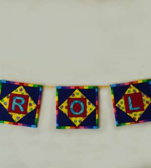 Coloured patchwork squares strung along a wall with name spelled out on centres